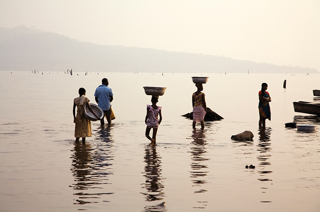 Ghanaians collecting water from Lake Volta at dusk.