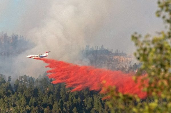 Fire retardants being sprayed from a jet over wildfires in California forests