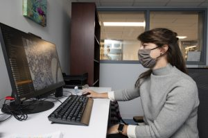 Amanda Martinot wearing a mask sitting at her desk in front of her computer