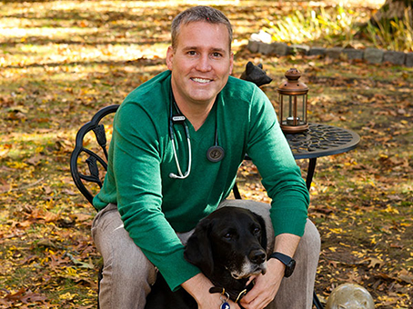 Dan Hebert with his black labrador retriever, Joe