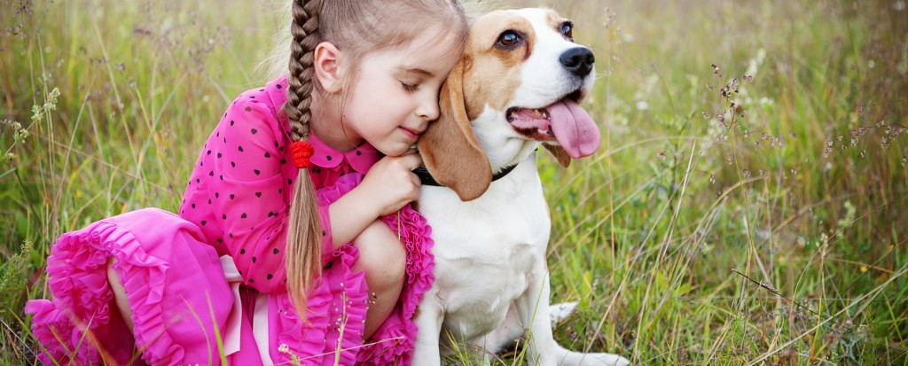little girl hugs her dog outdoors